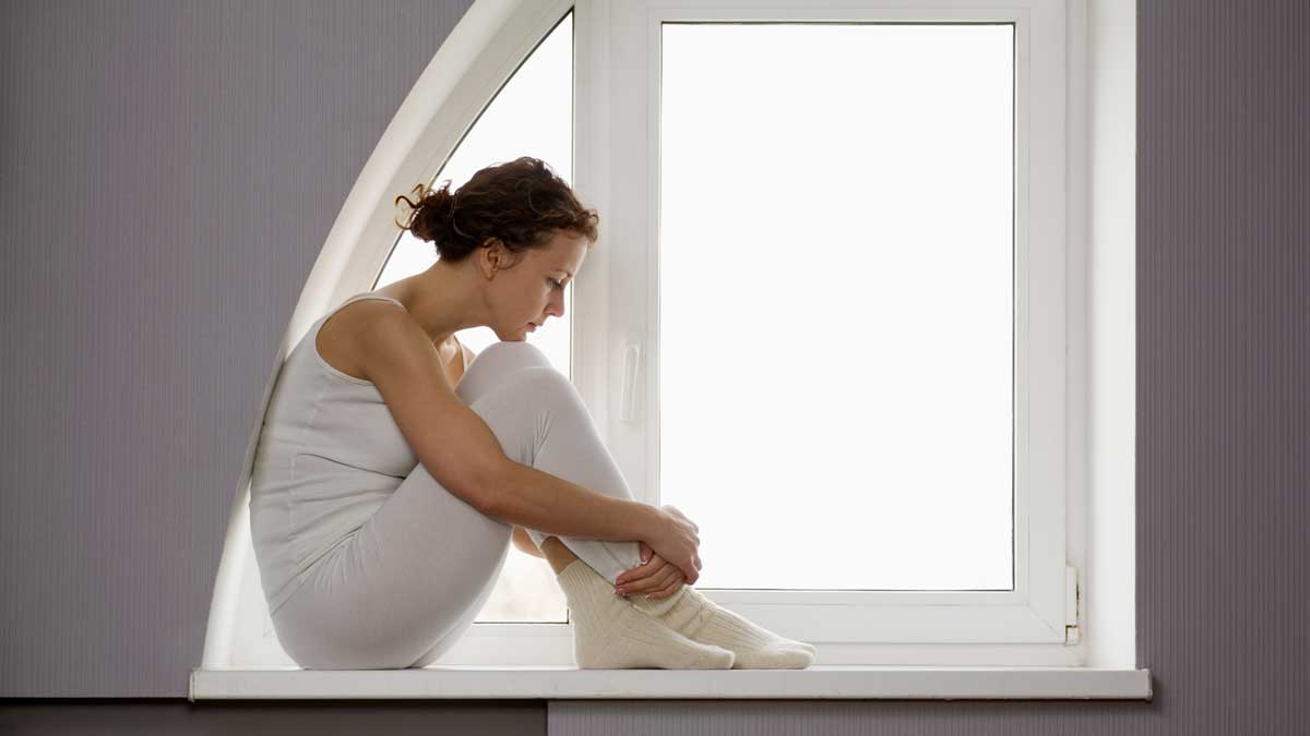 woman sitting on window edge