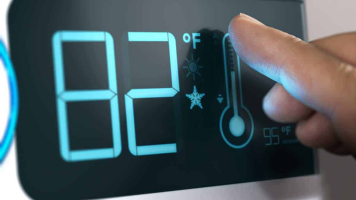 person touching smart thermostat