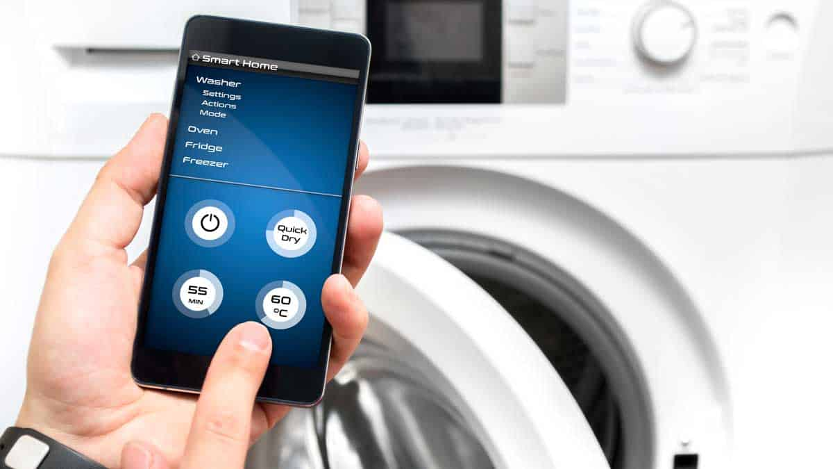 man uses smartphone for washing machine
