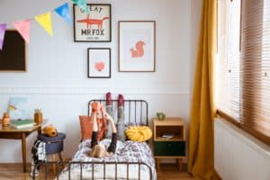 Cute vintage style posters on white wall of trendy bedroom for child