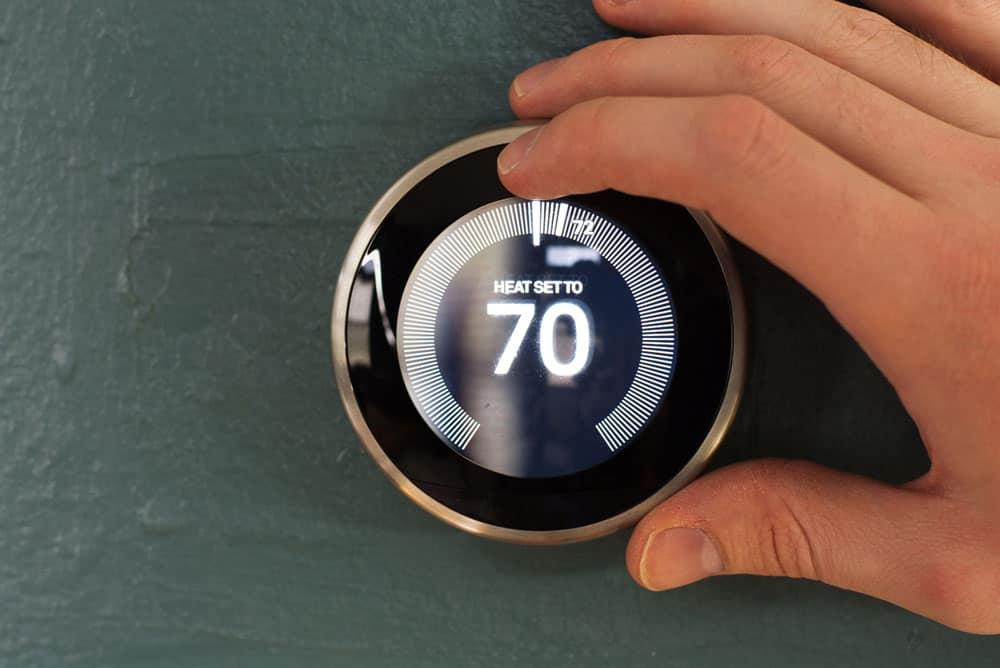 person adjusting Nest smart home thermostat