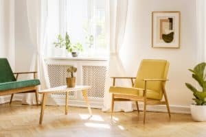 Yellow, retro armchair and a green sofa by a big, sunny window i