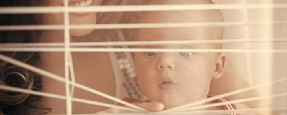 baby with mother looking thru blinds