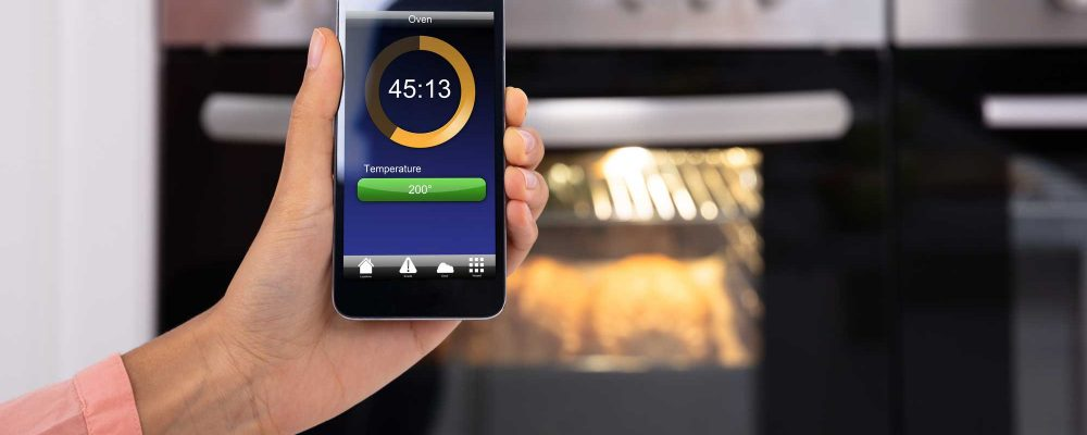 lady controlling smart oven with smart phone